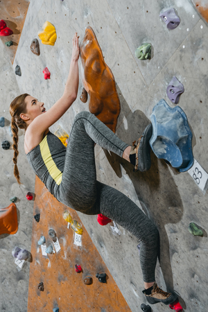 Full-length shot of young woman in sportive attire climbing a wall with grips at gym