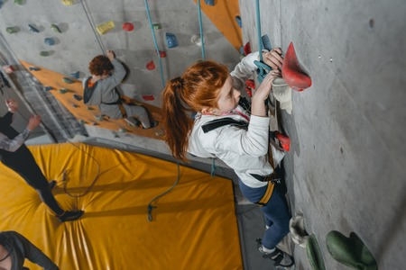 High angle shot of little girl in a harness climbing a wall with grips at gym Stock Photo