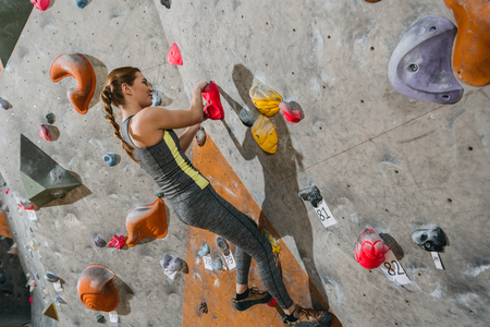 Full-length shot of young woman in sportive attire climbing a wall with grips at gym Stock Photo - 102812390