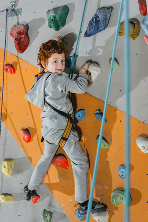 Full-length shot of little boy in a harness climbing a wall with grips at gym and looking at camera Stock Photo