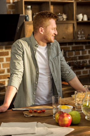 smiling man looking away while leaning on table with food in kitchen