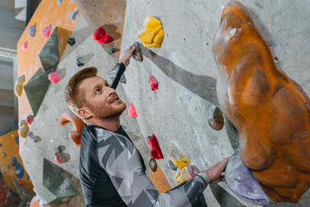 half-length shot of young man in sportive attire climbing a wall with grips at gym Stock Photo - 102812516