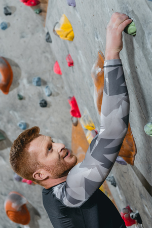 Closeup shot of young man in sportive attire climbing a wall with grips at gym