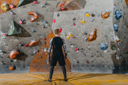 Full-length shot of a young man in sportive attire posing in front of climbing wall