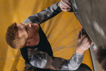 high-angle shot of young man in sportive attire climbing a wall with grips at gym Stock Photo - 102812532