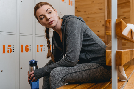Woman in sportive attire sitting on bench in locker room with water bottle and looking aside