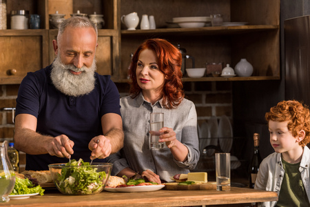 portrait of grandparents cooking salad and little boy sitting at table Standard-Bild