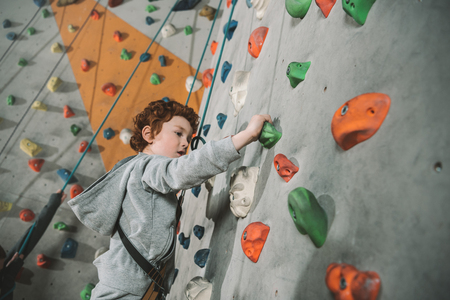 Half-length shot of little boy in a harness climbing a wall with grips at gym Stock Photo