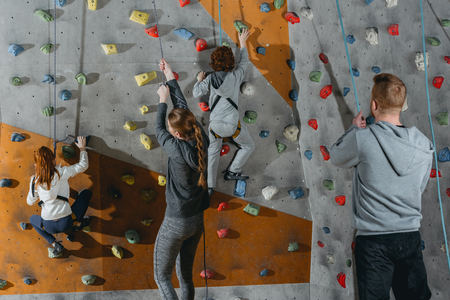 Two little kids climbing a wall at gym and their mother and father holding securing ropes 写真素材
