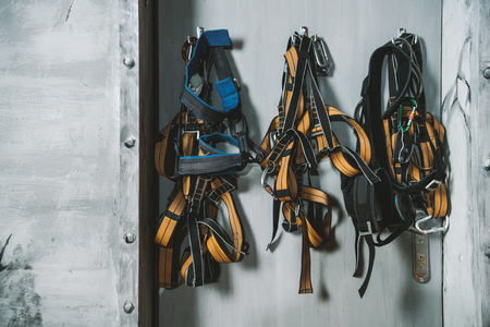Climbing harnesses hanging on the wall at the gym Stock Photo