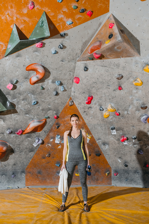 Full-length shot of a young woman in sportive attire posing in front of climbing wall Stok Fotoğraf