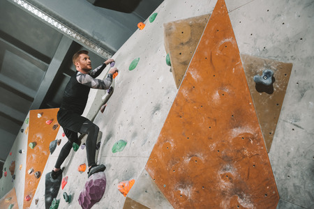 Full-length shot of young man in sportive attire climbing a wall with grips at gym  Stock Photo
