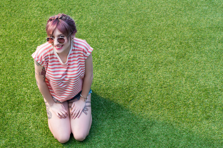 attractive young woman in sunglasses smiling at camera while kneeling on green grass Banco de Imagens