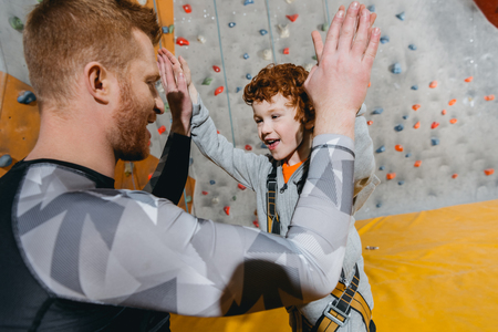 Closeup shot of little boy in harness high-fiving his dad with climbing walls in the bacackground