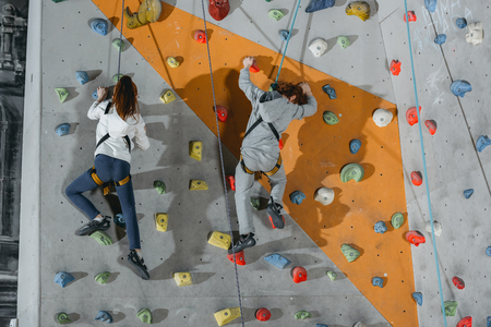 Full-length shot of two little kids in harnesses climbing a wall with grips at gym Stock Photo
