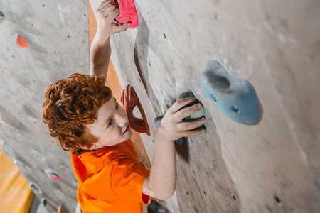 High-angle shot of little red-headed boy climbing a wall with grips