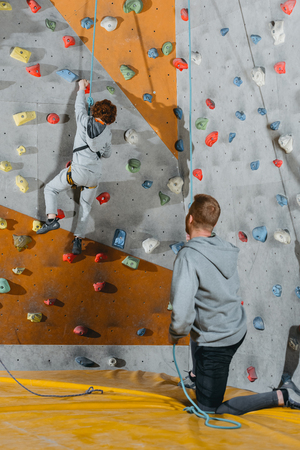 Full-length shot of little boy climbing a wall with grips at gym and his father holding securing rope
