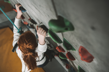 High-angle shot of little red-headed girl climbing a wall with grips at gym
