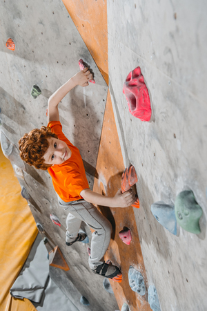 High-angle shot of little red-headed boy climbing a wall with grips and looking at camera Фото со стока