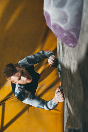 High angle shot of young man in sport attire, prepared to climb a wall with grips at gym