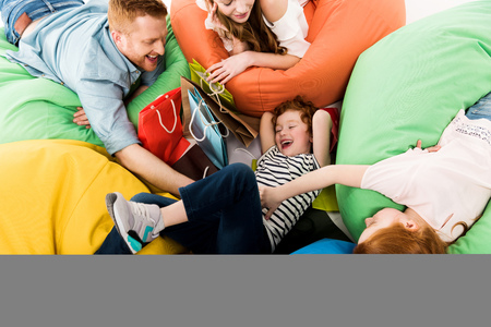 high angle view of happy family with shopping bags having fun on bean bag chairs
