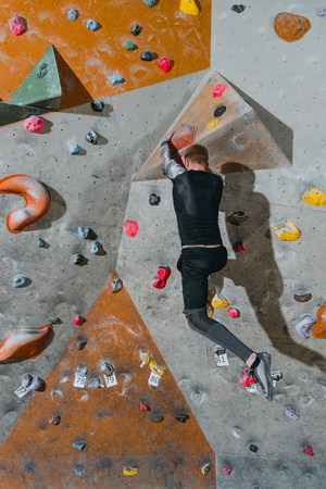 Rear view shot of young man in sportive attire climbing a wall with grips at gym