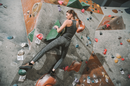 Full-length shot of young woman in sportive attire climbing a wall with grips at gym Stock Photo - 102812946