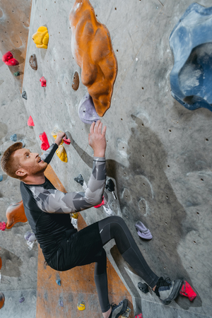 Full-length shot of young man in sportive attire climbing a wall with grips at gym Stock Photo - 102812949