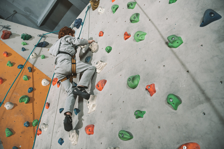 Low-angle shot of little red-headed boy climbing a wall