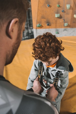 Half-length shot of dad securing his little son in a climbing harness in gym
