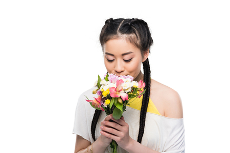 beautiful asian girl with closed eyes smelling flowers isolated on white Stock Photo
