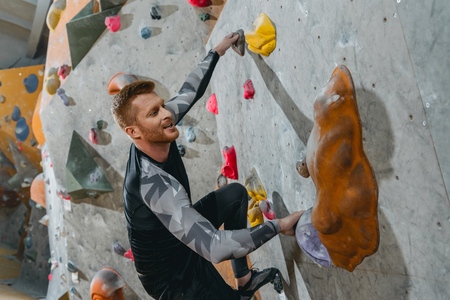 Young man in sportive attire climbing a wall with grips at gym