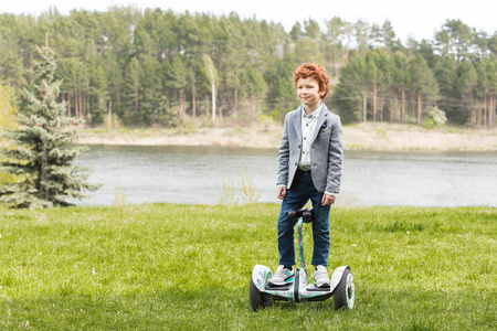 adorable red haired boy riding gyroscooter outdoors Stock Photo