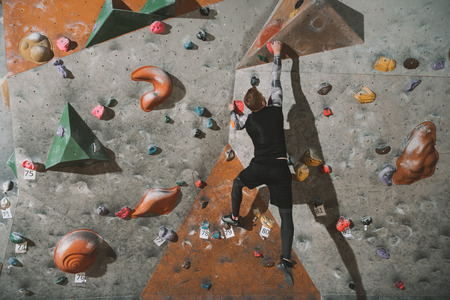Rear view shot of young man in sport attire climbing a wall with grips at gym