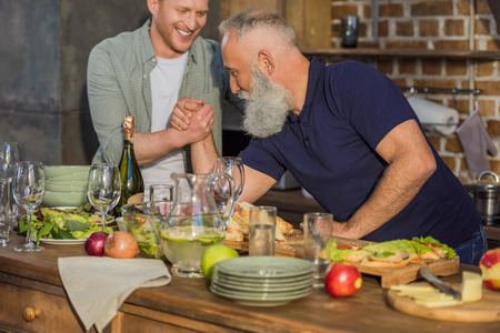 side view of senior father and adult son arm wrestling together in kitchen at home Banque d'images - 102813220