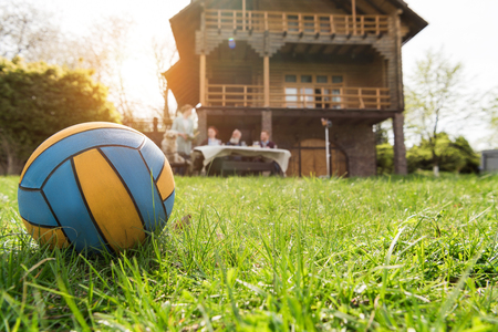 close-up view of leather ball on green grass and family spending time together near country house Stock fotó