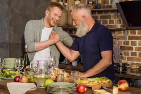 side view of senior father and adult son arm wrestling together in kitchen at home Banque d'images - 102813224