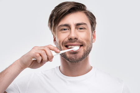 happy man brushing teeth and looking at camera, isolated on white