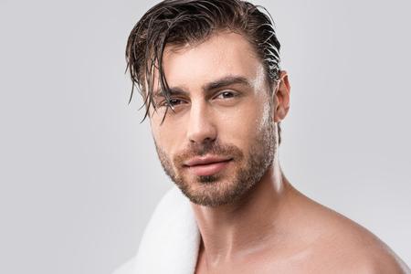 hübscher Mann mit nassen Haaren und Handtuch, isoliert auf grau Standard-Bild