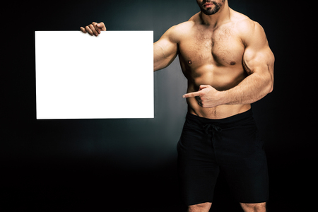 partial view of shirtless athletic man pointing at blank banner in hand isolated on black Banque d'images - 102813395