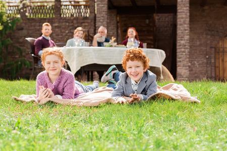 selective focus of kids resting on green grass while family having dinner