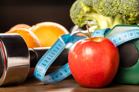 close up view of healthy food, measuring tape and dumbbells, healthy living concept