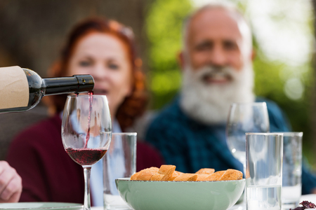 selective focus of senior couple looking at pouring red wine into glass process