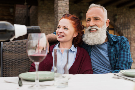 portrait of happy senior couple sitting at table during dinner at countryside