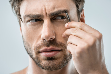 handsome man plucking eyebrows with tweezers, isolated on grey