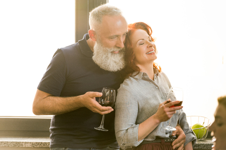 portrait of senior man hugging smiling wife while holding glasses of wine at home 版權商用圖片