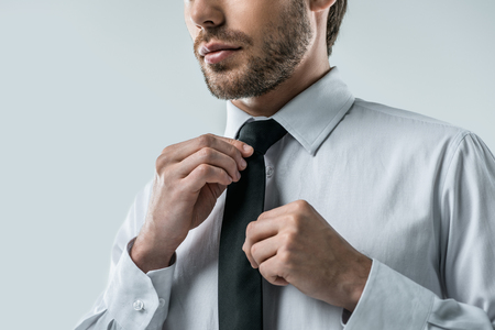 cropped view of businessman in white shirt wearing tie, isolated on grey Stock Photo