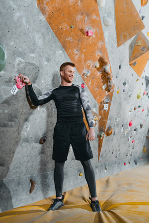Full-length shot of a young man in sportive attire standing near a climbing wall and looking aside Stock Photo