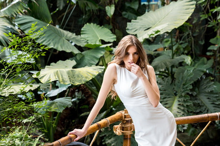seductive woman in white dress posing in tropical park