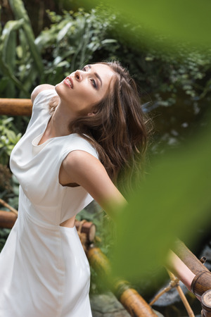 attractive sensual woman in white dress posing in tropical orangery Stock Photo